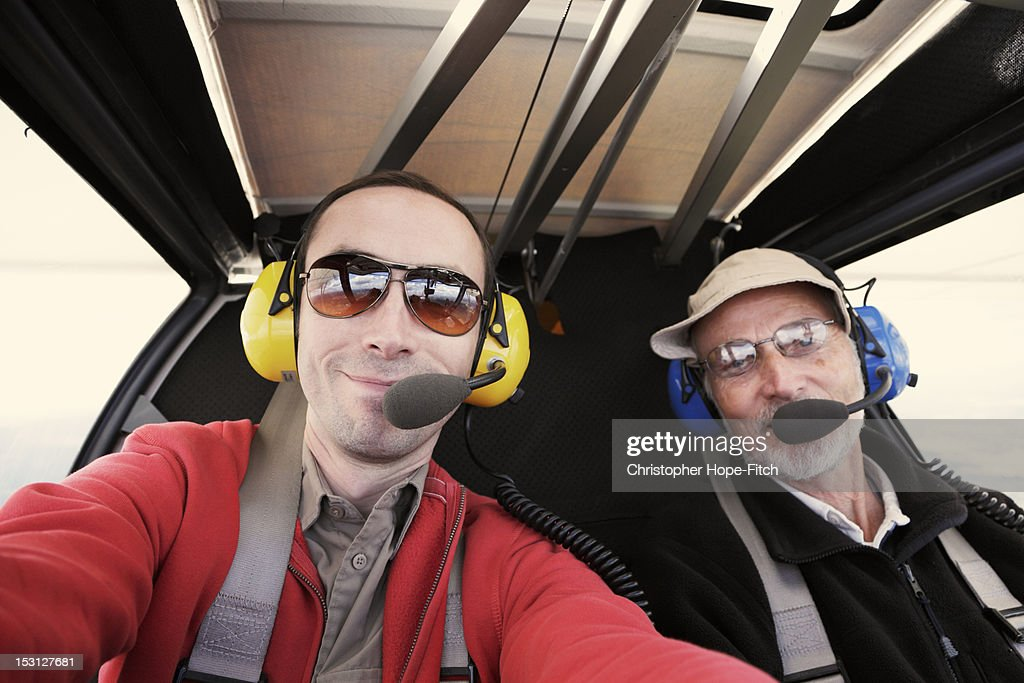 Close-up of father and son wearing headphones and sunglasses flying in light aircraft.