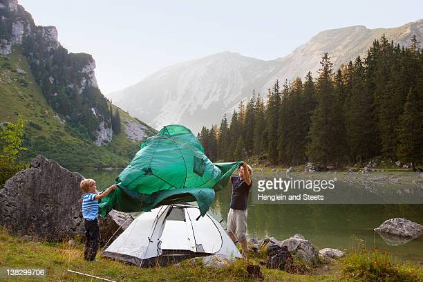 father and son pitching a tent by lake - tarpaulin stock pictures, royalty-free photos & images