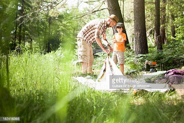 Father and son pitching tent in forest