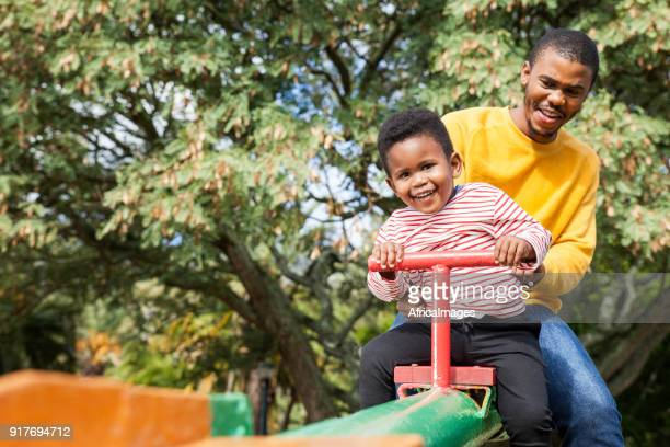 Father and son play on a seesaw at the park.