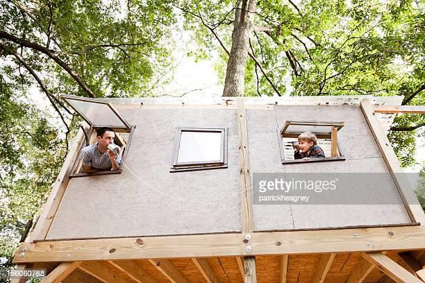 Père et fils jouer au téléphone dans une maison dans un arbre