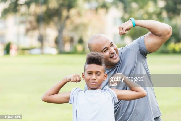 father and son playfully flexing muscles - flexing muscles stock pictures, royalty-free photos & images