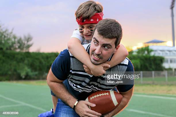 father and son playing american football - football league stock pictures, royalty-free photos & images