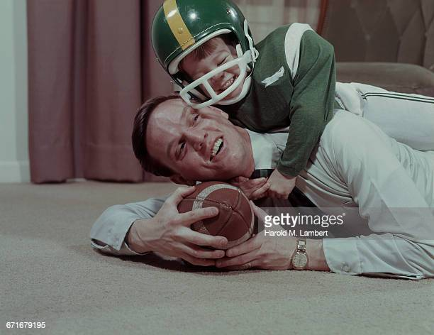 father and son playing american football  - {{ contactusnotification.cta }} stockfoto's en -beelden