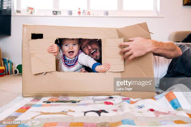 father and son playing at home with a cardboard box - playing stock-fotos und bilder