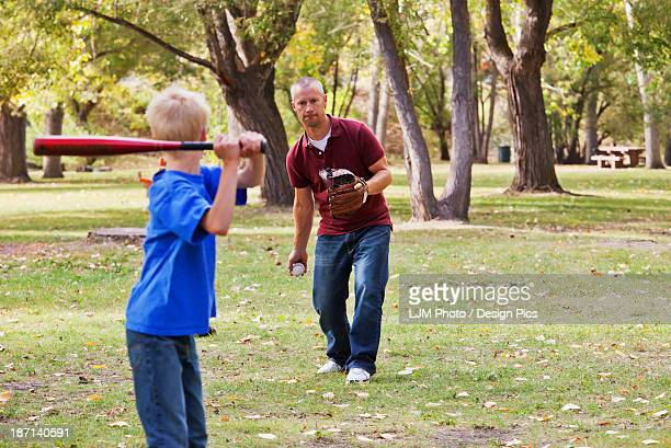 father and son playing baseball in a park - blue balls pics stock pictures, royalty-free photos & images
