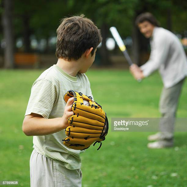 Father and son (10-11) playing baseball in park