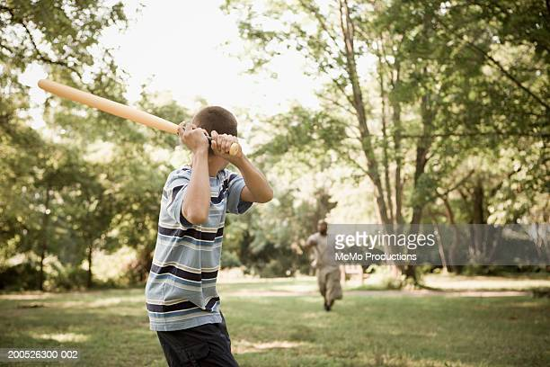 Father and son (10-12) playing baseball in park, rear view