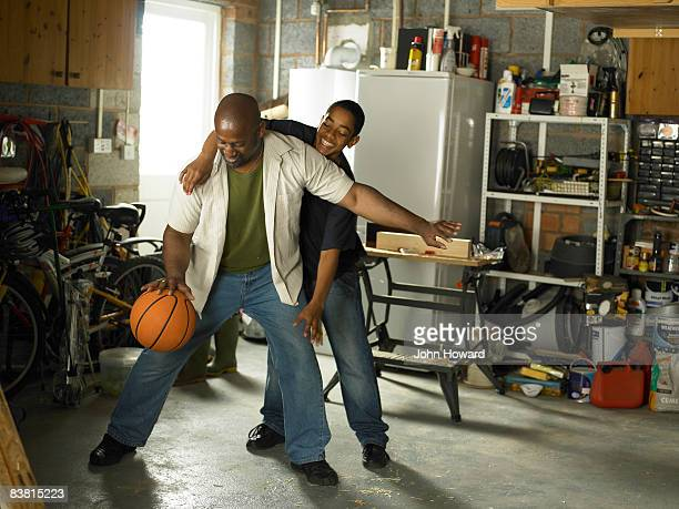 Father and Son playing basketball in garage