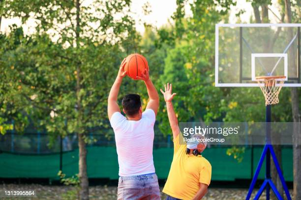 father and son playing basketball in the park - shooting baskets stock pictures, royalty-free photos & images
