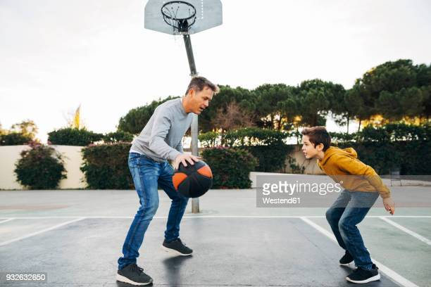 father and son playing basketball on an outdoor court - sporting term stock-fotos und bilder