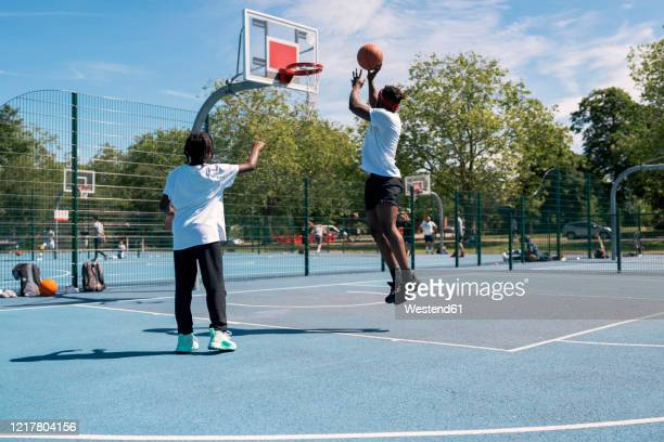 father and son playing basketball on basketball court - try scoring stock pictures, royalty-free photos & images