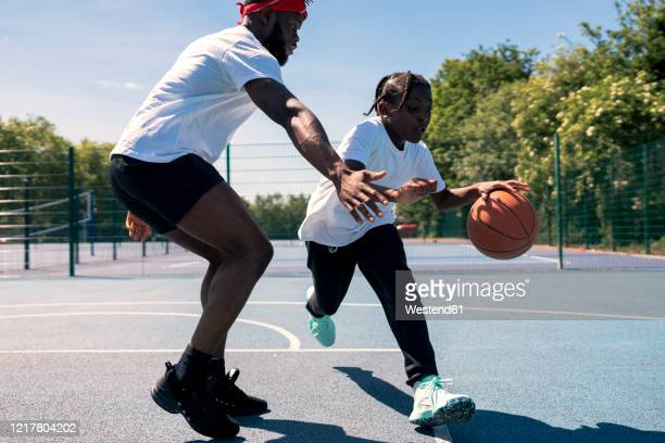 father and son playing basketball on basketball court - sporting term stock pictures, royalty-free photos & images