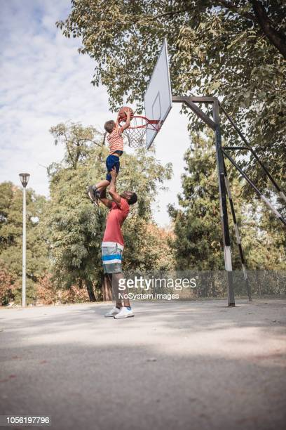 padre e hijo jugando baloncesto - encestar fotografías e imágenes de stock
