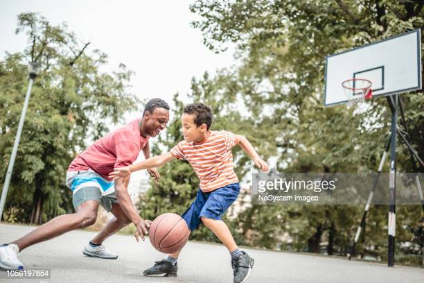 father and son playing basketball - dribbling sports stock pictures, royalty-free photos & images