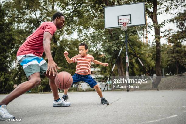 father and son playing basketball - shooting baskets stock pictures, royalty-free photos & images