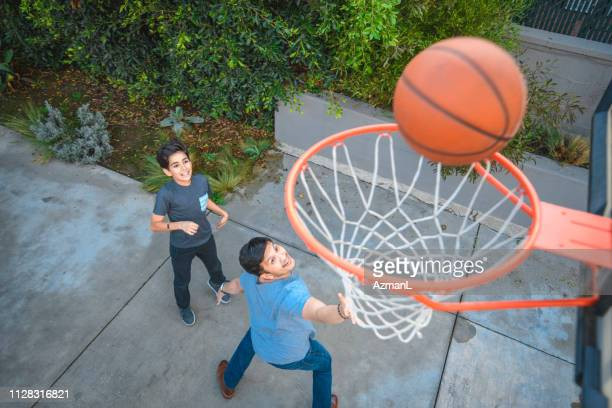 father and son playing basketball - making a basket scoring stock pictures, royalty-free photos & images