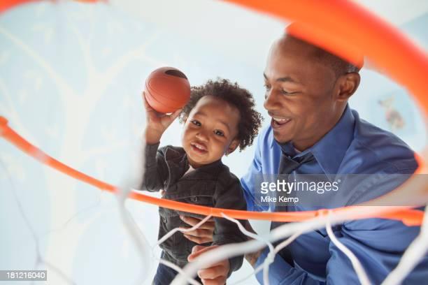 father and son playing basketball together - encestar fotografías e imágenes de stock