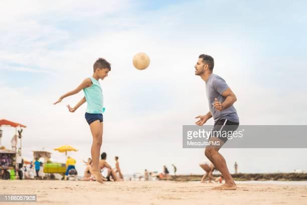 ブラジルのペルナンブコ州ポルト・デ・ガリーニャスでビーチサッカーをしている父と息子。 - ビーチサッカー ストックフォトと画像