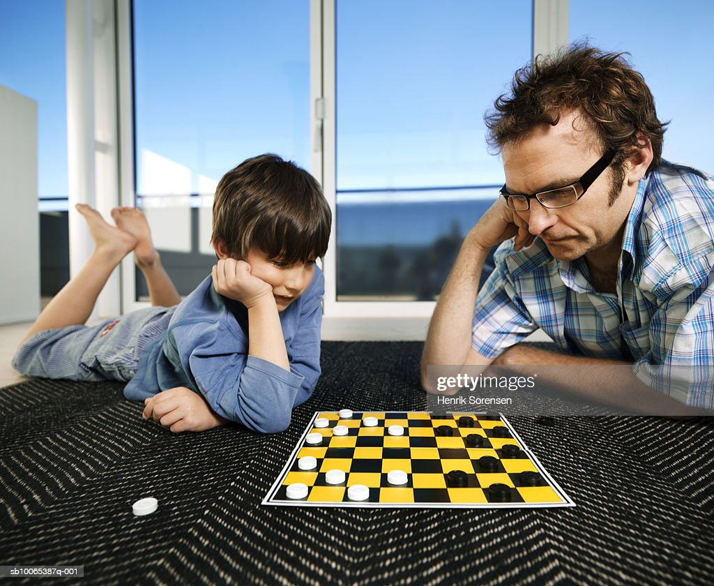 Father and son (8-9) playing board game on carpet : Foto stock