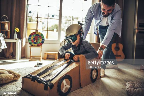 father and son playing car racing with cardboard boxes - family with one child stock pictures, royalty-free photos & images