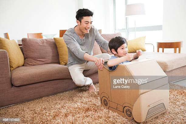Father and son playing carton car in living room