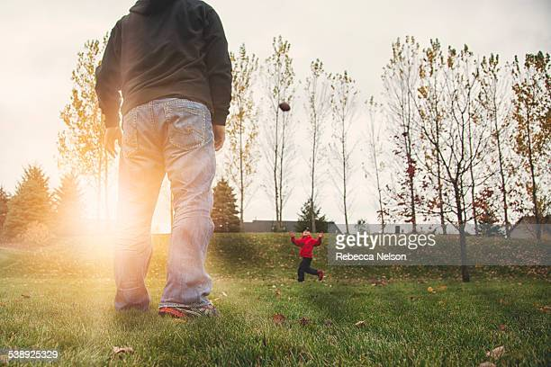 Father and son playing catch with football