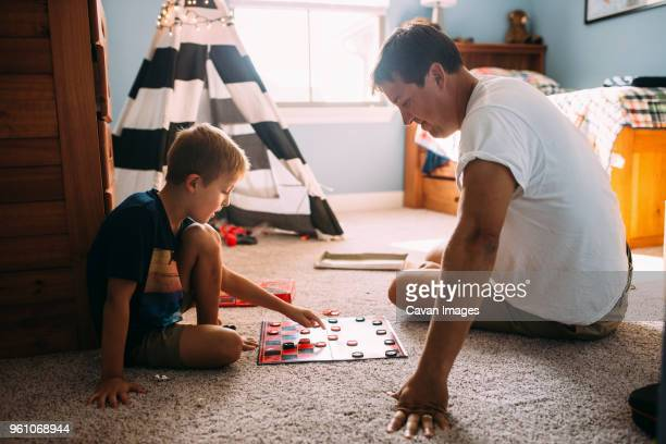 father and son playing checkers while sitting on carpet at home - board game stock pictures, royalty-free photos & images