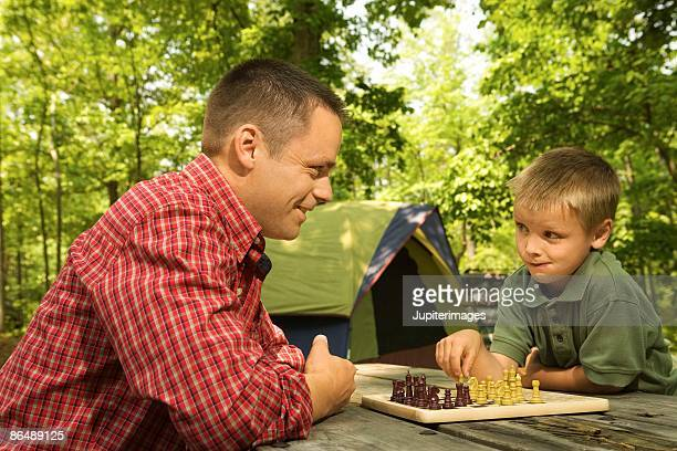 Father and son playing chess at campsite