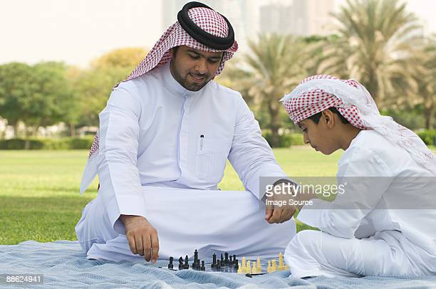 a father and son playing chess in a park - uae heritage stock photos and pictures