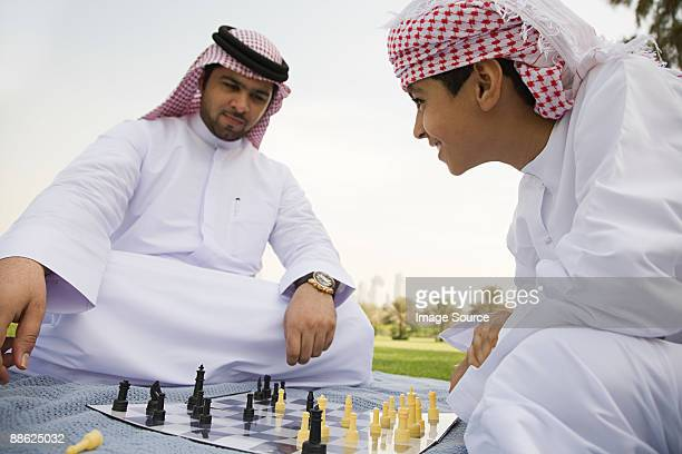 A father and son playing chess in a park