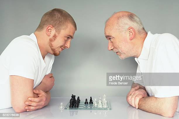 father and son playing chess - face to face stock pictures, royalty-free photos & images