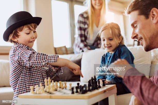 father and son playing chess - tag game stock photos and pictures