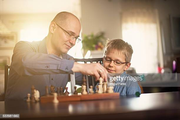 Father and son playing chess together