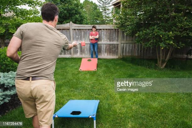 father and son playing corn hole game in the backyard together. - vegetais - fotografias e filmes do acervo