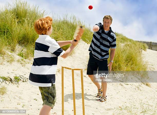 father and son (8-9) playing cricket on beach - beach cricket stock pictures, royalty-free photos & images