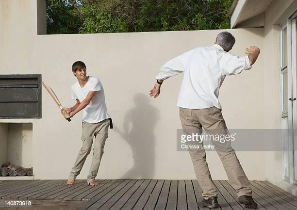 Père et fils jouant sur le patio de cricket