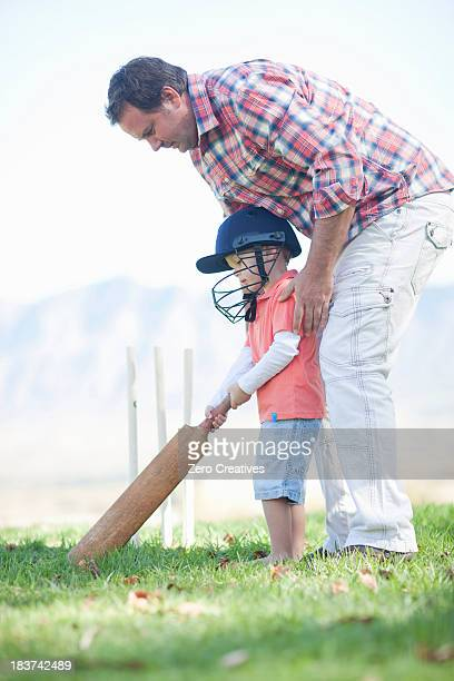 father and son playing cricket - cricket bat stock pictures, royalty-free photos & images
