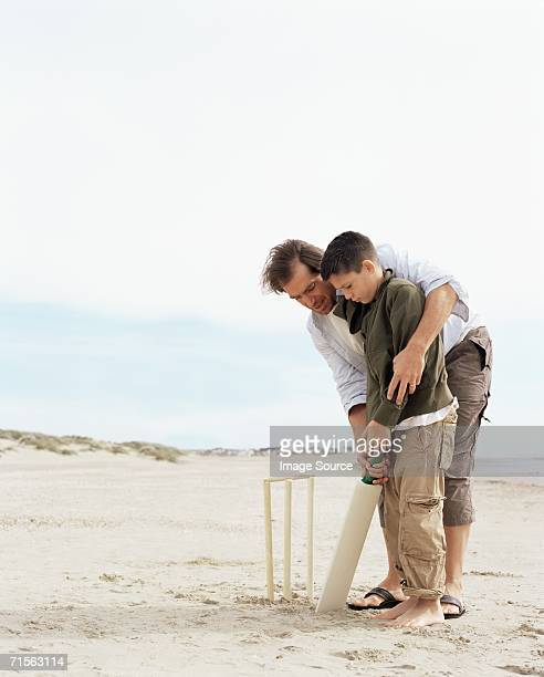 father and son playing cricket - beach cricket stock pictures, royalty-free photos & images
