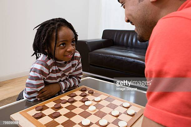 father and son playing draughts - chequers stock photos and pictures