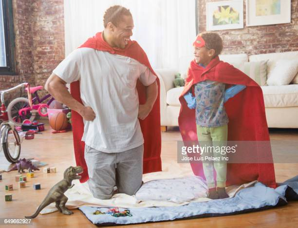 Father and son playing dress-up in living room