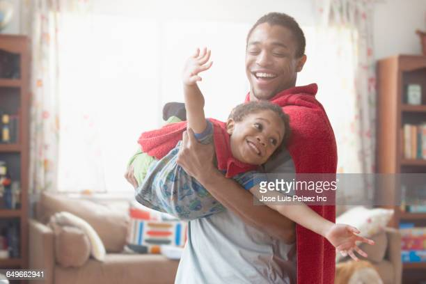 father and son playing dress-up in living room - hero stock photos and pictures
