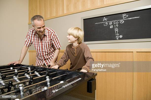 Father and son playing foosball together at home