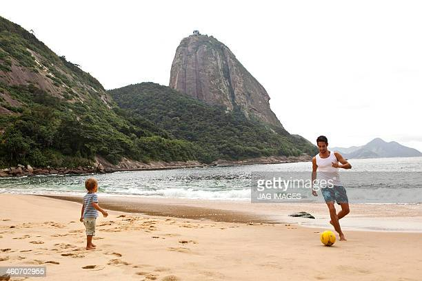 Father and son playing football on beach, Rio de Janeiro, Brazil