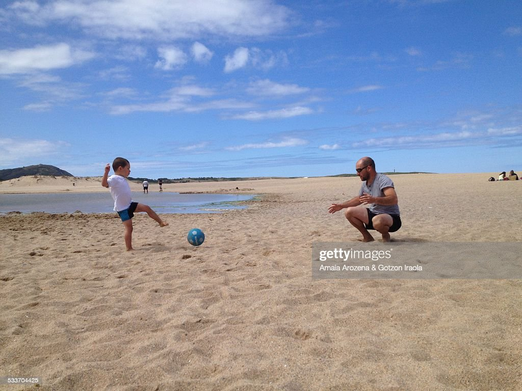 Father and son playing football on the beach : Foto stock