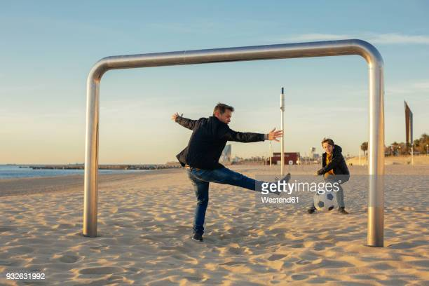 father and son playing football on the beach - scoring a goal stock pictures, royalty-free photos & images
