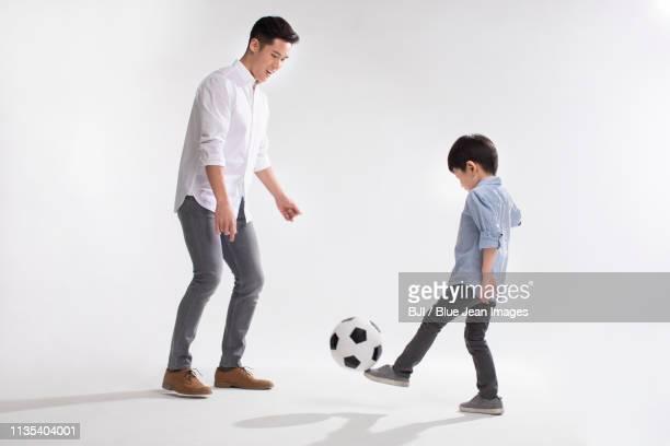 father and son playing football - schoppen lichaamsbeweging stockfoto's en -beelden