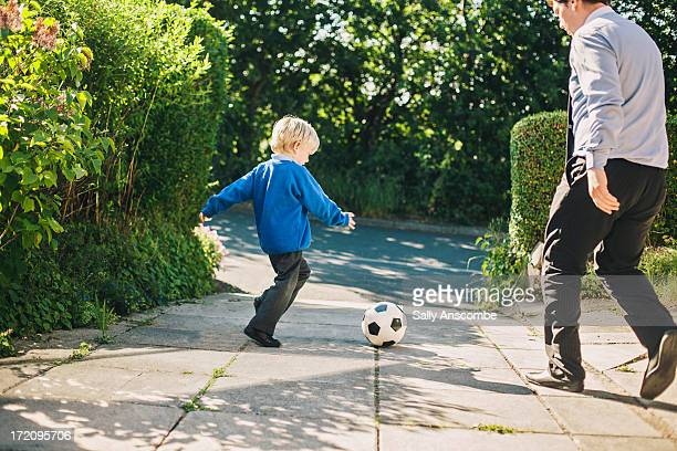 father and son playing football together - drive ball sports stock pictures, royalty-free photos & images