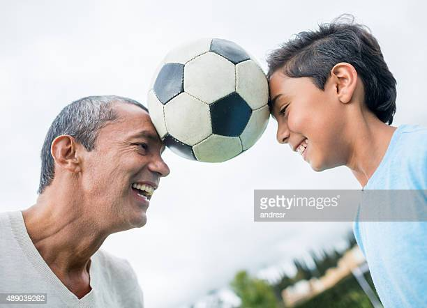 father and son playing football together - head coach stockfoto's en -beelden