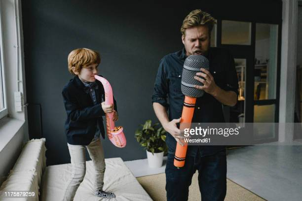 father and son playing fun instruments - humor stock-fotos und bilder